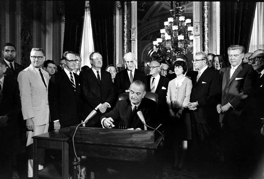 FILE - In this Aug. 6, 1965, photo, President Lyndon Baines Johnson signs the Voting Rights Act of 1965 in a ceremony in the President's Room near the Senate Chambers on Capitol Hill in Washington. Three years ago, the Supreme Court warned there could be constitutional problems with a landmark civil rights law that has opened voting booths to millions of African-Americans. Now, opponents of a key part of the Voting Rights Act are asking the high court to finish that provision off.  Surrounding the president from left directly above his right hand, Vice President Hubert Humphrey; House Speaker John McCormack; Rep. Emanuel Celler, D-N.Y.; first daughter Luci Johnson; and Sen. Everett Dirksen, R-Ill.  Behind Humphrey is House Majority Leader Carl Albert of Oklahoma; and behind Celler is Sen. Carl Hayden, D-Ariz.  (AP Photo) Photo: Associated Press