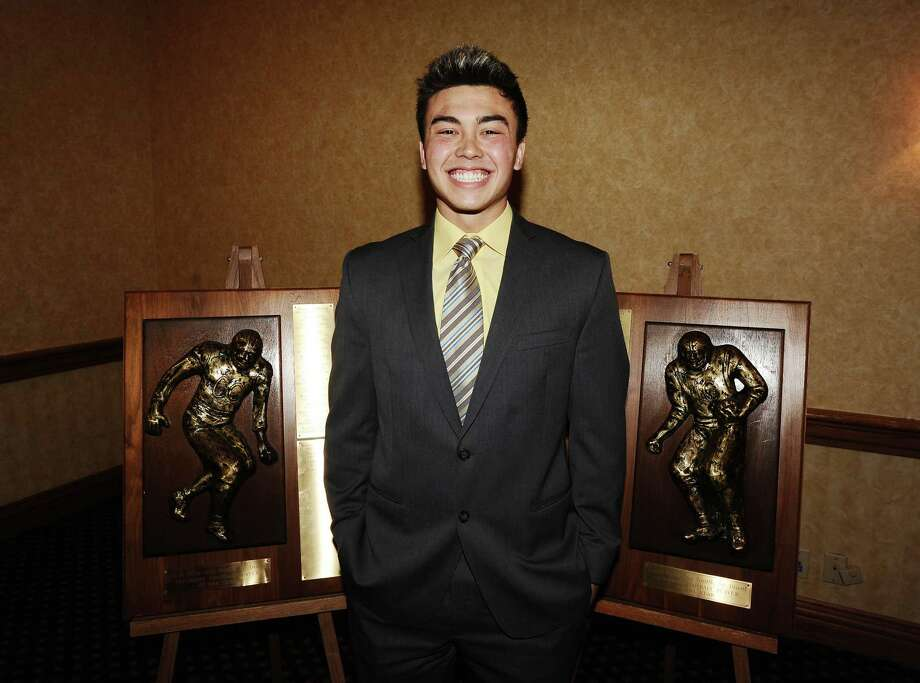 2012 offensive and defensive winner for the Coach Willie Ray Smith, Sr. Award, Montana Quirante, from Vidor High School stands next to the awards at the MCM Elegante' on Wednesday, February 20, 2013.  Photo taken: Randy Edwards/The Enterprise Photo: Randy Edwards