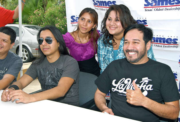 Top Vanesa Reyes and Pola Varela smile as they take a picture with Viktor Pacheco and Oscar De La Rosa from La Mafia during an autograph session. File photo Photo: Ulysses S. Romero / Laredo Morning Times