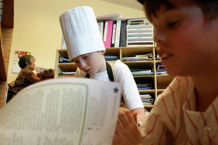 Isaac Gateno, left, 11, dressed as a chef, and Avi Moses, 11, dressed as a baseball player, do their classwork for Purim at the Robert M. Beren Academy. Photo: Johnny Hanson, Staff / © 2013  Houston Chronicle