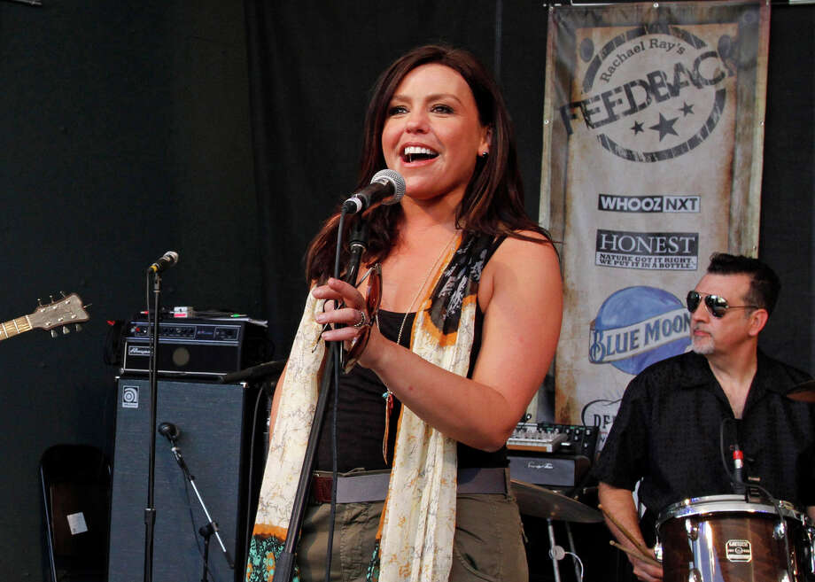 FILE - This March 19, 2011 file photo shows Rachael Ray introducing a band at her Feedback side party during the SXSW Music Festival in Austin, Texas. The author and Emmy-winning chef is getting ready for next month's South by Southwest Festival in Austin, Texas, where she again will be hosting all-day music performances, with more than a dozen bands. One of those bands, The Cringe, is led by her husband, John Cusimano. (AP Photo/Jack Plunkett, file) Photo: Jack Plunkett