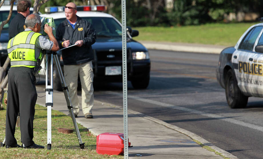 San Antonio police examine the scene of a hit and run accident Thursday February 21, 2013 on Sir Winston Street near Blanco Road. Police said a woman carrying a bag of groceries was hit by a person driving a van who fled from the scene. Police are questioning a possible suspect. Photo: JOHN DAVENPORT, San Antonio Express-News / ©San Antonio Express-News/Photo Can Be Sold to the Public