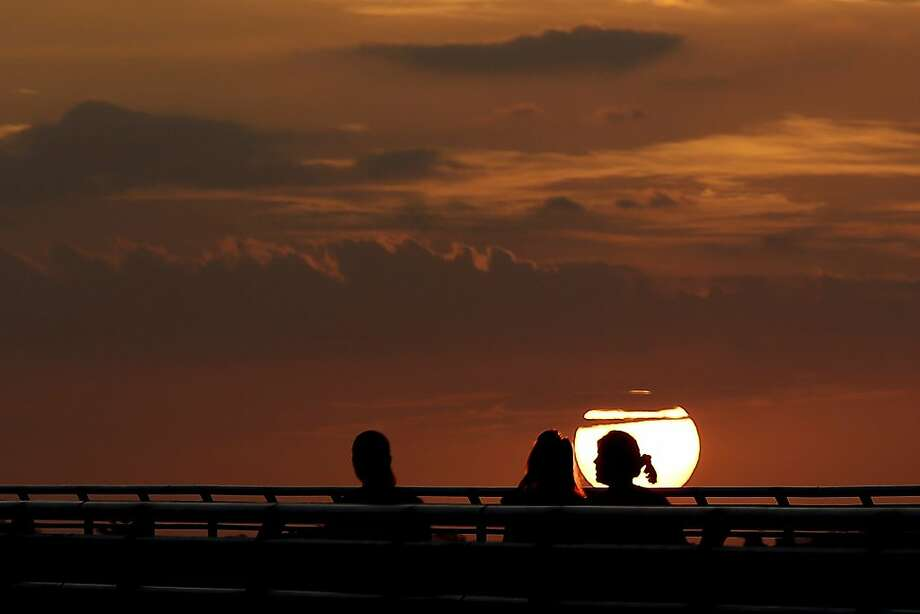 Sky aglow: Three women take in the sunset on the Ocean Boulevard causeway in Stuart, Fla. Photo: Julio Cortez, Associated Press