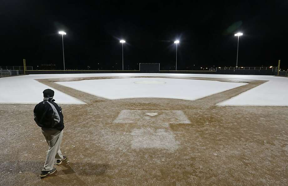Winter drops in on spring training: Colorado Rockies ground crew member Ruben Rush checks out a snow-dusted diamond at the Salt River Fields baseball park in sunny Scottsdale, Ariz. Photo: Darron Cummings, Associated Press