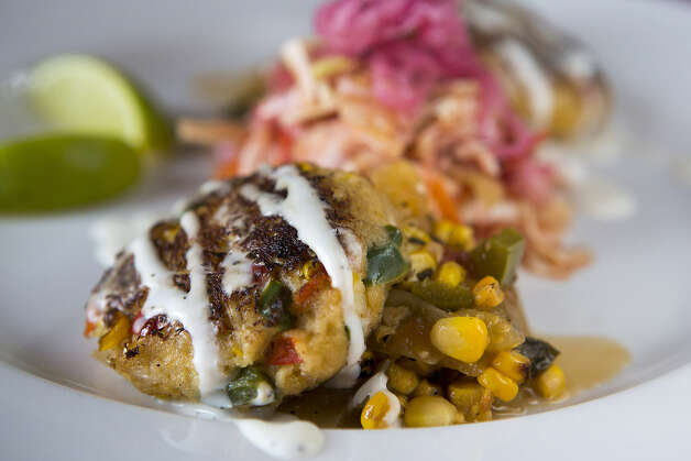 Crab cakes offer a fresh flavor. Spicy corn relish and pickled onions accompany.