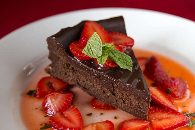 Tequila chocolate cake is served with fresh strawberries in a light sauce.