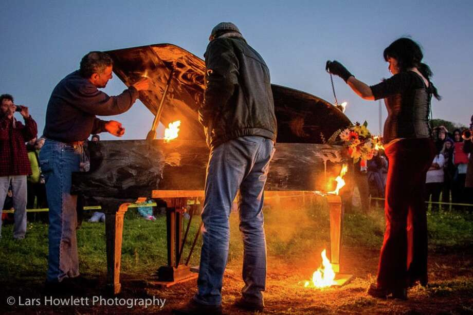 Helpers start to light the piano on fire as the sun sets.