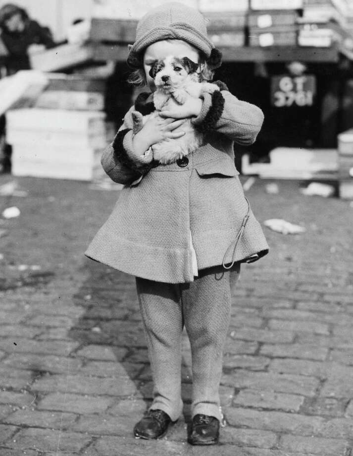A little girl carries a struggling puppy away from a market where she has just bought him, 1938. Photo: Fox Photos, Getty Images / Hulton Archive