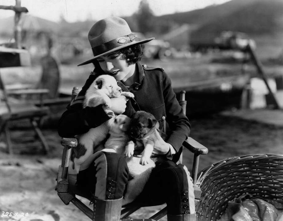 French actress Renee Adoree wearing a Mountie's uniform and cuddling a litter of puppies which were born on the set of the MGM film 'Rose Marie' in 1928. Photo: Margaret Chute, Getty Images / Moviepix