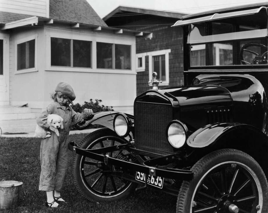 A young girl with a puppy under her arm polishes a 1922 Ford automobile with a sponge on the lawn of  home, 1923. Photo: American Stock Archive, Getty Images / Archive Photos