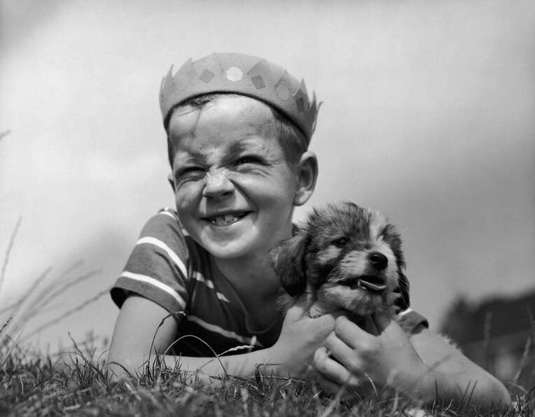 A boy in a Jughead hat lying on a lawn holding a puppy, 1945.
