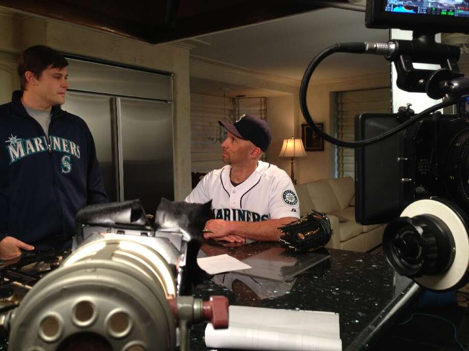 Mariners outfielder Raul Ibanez gets some tips while shooting a TV commercial.