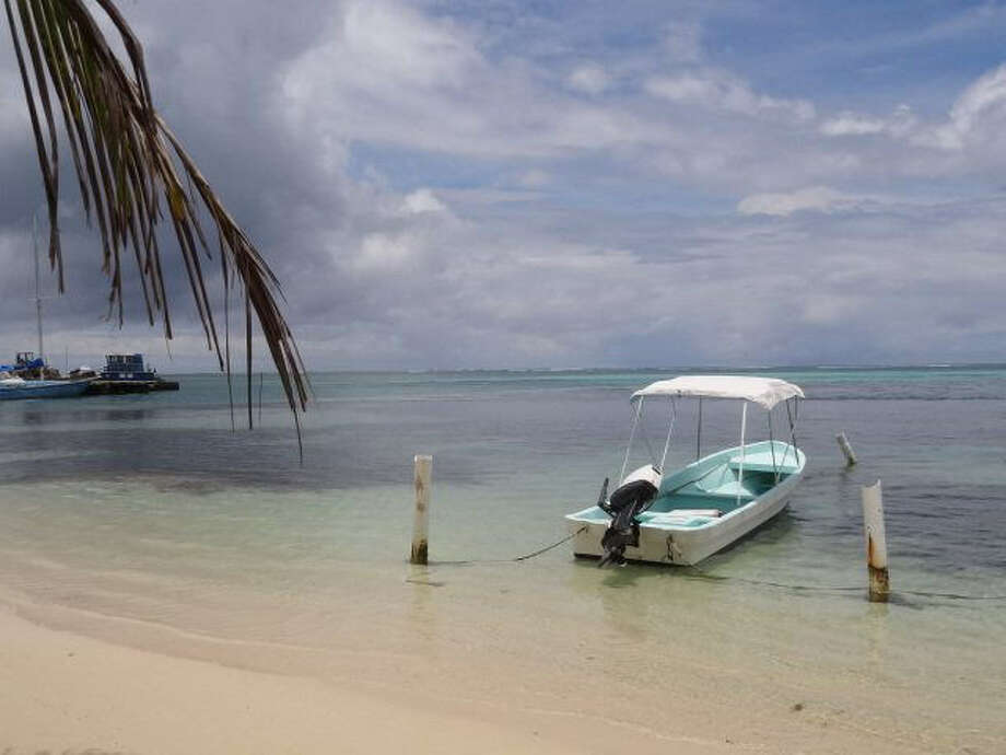 The beaches along San Pedro, Belize, are peaceful, but clouds threaten another shower. The area attracts snorkelers, drawn to the area by the Belize Barrier Reef. Photo: Photos By Sarah Sumadi / For The Express-News