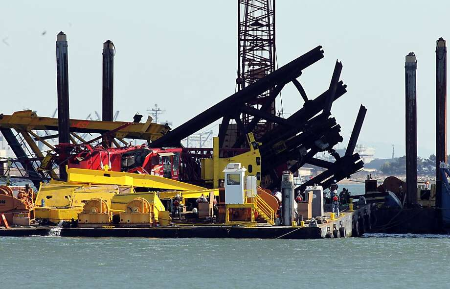 A construction crane removing the temporary supports under the eastern section of the new Bay Bridge toppled over this afternoon onto the barge that was carrying it in Oakland, Calif., on Thursday Feb. 21  2013. Photo: Michael Macor, The Chronicle