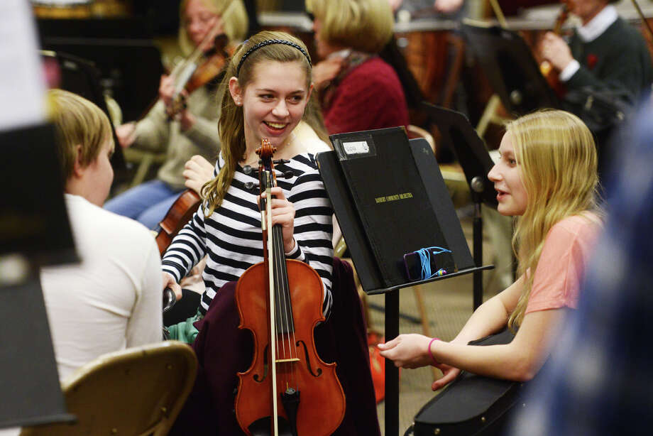 Anna Pinckney, center, 16, of Newtown, Conn., and Sara Lampel, 15, of Newtown, Conn., joke around before the Danbury Community Orchestra rehearsal at the Danbury Music Centre in Danbury, Conn. Wednesday, Feb. 20, 2013. Photo: Tyler Sizemore / The News-Times