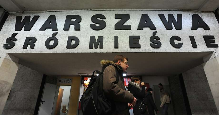 People walk under a board with the name of a train station with several Polish diacritical marks, in Warsaw, Poland, Thursday, Feb. 21, 2013. Polish language experts have launched a campaign, as part of the UNESCO International Mother Language Day, to preserve the challenging system of its diacritical marks, saying the tails, dots and strokes are becoming obsolete under the pressure of IT and speed. The name of the station reads Warsaw Downtown. (AP Photo/Alik Keplicz) Photo: Alik Keplicz, Associated Press