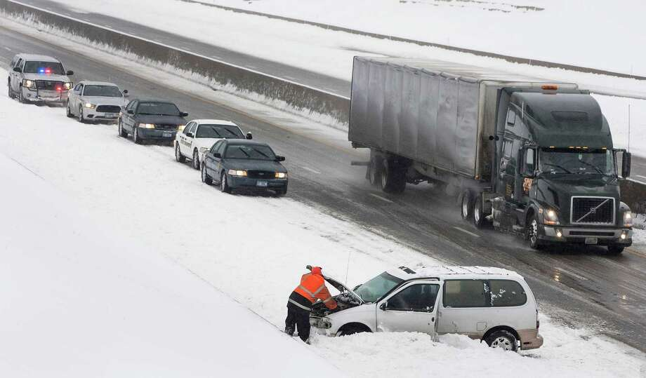 Emergency crews work to get a van out from the snow packed shoulder of I-70, Thursday afternoon Feb. 21, 2013 in Topeka, Kan. Kansas was the epicenter of the winter storm, with parts of the state buried under 14 inches of powdery snow, but winter storm warnings stretched from eastern Colorado through Illinois. Photo: AP