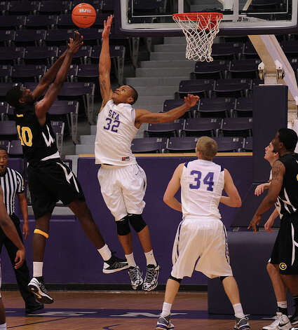 Stephen F. Austin senior forward Taylor Smith, a Clemens grad, tries to block a shot by Grambling center Peter Robinson in a 60-38 SFA victory on Dec. 20, 2012. Smith, who leads the nation in field-goal percentage, is among the top 10 in blocks per game. Photo: SFA Athletics, EN