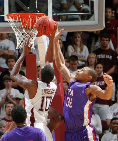 Stephen F. Austin's Taylor Smith (32) blocks a shot by Texas A&M;s David Loubeau (10) during the second half of an NCAA college basketball game on Saturday, Dec. 3, 2011, in College Station, Texas. Texas A&M won 55-42. (AP Photo/Jon Eilts) Photo: Jon Eilts, EN / FR170396 AP