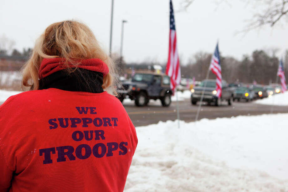 A woman shows her support for U.S. Army Staff Sgt. Mark Schoonhoven outside his funeral as the procession begins to leave St. Margaret's Catholic Church in Otsego, Mich., Thursday, Feb. 7, 2013. Schoonhoven, part of a unit out of Fort Carson, Colo. was wounded Dec. 15 when insurgents attacked his unit with an improvised explosive device in Kabul. He died Jan. 20 at Brooke Army Medical Center at Fort Sam Houston, Texas. (AP Photo/Kalamazoo Gazette, James Buck) Photo: James Buck, Associated Press / Kalamazoo Gazette