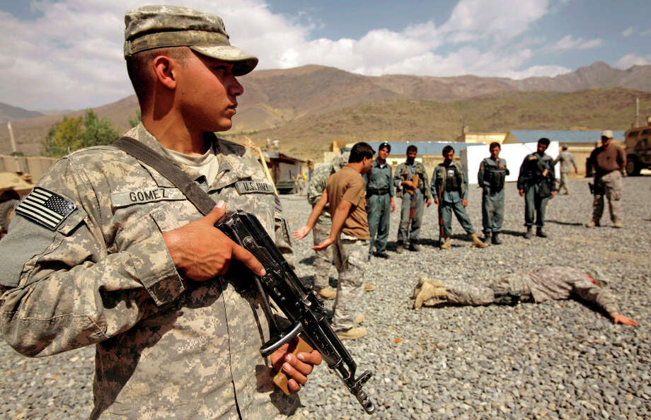 FILE - In this Saturday, Sept. 19, 2009 file photo, U.S. Army Sgt. German Gomez, 23, from Houston, Texas, of the 118th Military Police Co., based at Fort Bragg, N.C., stands guard during a training session for Afghanistan National Police at their combat outpost in the Jalrez Valley in Afghanistan's Wardak Province. Hundreds of soldiers have been detained or removed from the Afghan National Army in 2012 after a surge in insider attacks against foreign forces who are their supposed partners in the fight against Taliban insurgents and other militants. The Afghan officials say they are re-vetting soldiers to stem the attacks that threaten to unravel the international community's alliance with the fragile government trying to stand on its own as foreign troops withdraw.(AP Photo/Maya Alleruzzo, File) Photo: Maya Alleruzzo, Associated Press / AP