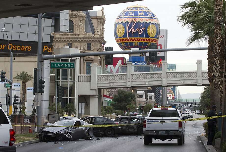 Police rope off the crime scene on the Strip. Authorities say someone in a Range Rover shot at people in a Maserati that then crashed into a taxi. The cab burst into flames, and the driver and passenger were killed. Photo: Steve Marcus, Associated Press