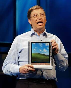 Gates holds a Tablet PC at the announcement of the availability of the devices and Windows XP Tablet PC operating system in 2002 in New York. Photo: STAN HONDA, Getty / AFP