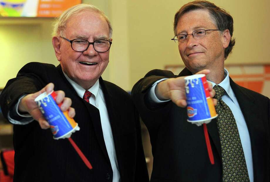 US billionaire investor Warren Buffett (L) and Microsoft founder Bill Gates (R) flip over their Dairy Queen Blizzard treats, the most successful product ever released in the history of Dairy Queen, a US desert chain with over 300 stores in China, at the opening of a new branch in Beijing on September 30, 2010.  Gates and Buffett hosted a banquet the previous night for China's super rich that sparked debate about Chinese philanthropy, amid reports that wealthy invitees had been reluctant to attend. The two, who have already persuaded 40 wealthy US individuals to hand over more than half of their fortunes, had insisted they would not pressure attendees for money and simply wanted to learn about charity in China. Buffett is the CEO of Berkshire Hathaway which owns Dairy Queen. AFP PHOTO/Frederic J. BROWN Photo: FREDERIC J. BROWN, Getty / 2010 AFP