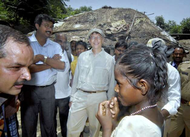 Bill Gates smiles as he and his entourage visit Gularia village in Khagaria, about 170 km from Patna, on May 12, 2010. Gates on May 12 visited the village inhabited mainly by low-caste dalits (untouchables) during his stay in India's Bihar state, one of the country's poorest states. AFP PHOTO/STR Photo: STR, Getty / 2010 AFP