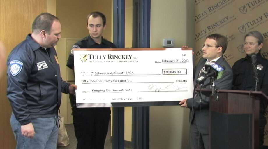 David Dean, left, of the Schenectady County SPCAaccepts a check for more than $50,000 is presented by Rinckey to the Schenectady County SPCA from the Albany law firm Tully Rinckey. (Submitted photo)