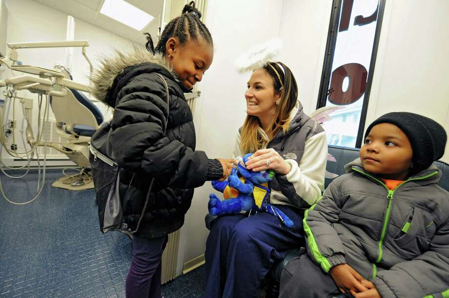 Elizabeth Burrill, of St. Peter's Hospital, teaches Jahleya Wilson, 7, of Albany how to brush using a stuffed dinosaur in the St. Peter's Hospital Ronald McDonald Care Mobile outside the Arbor Hill Community Center on Thursday Feb. 21, 2013 in Albany, N.Y.  Josiah Wilson, 4, waits to the right. Clinicians were available to guide children and their parents and answer questions on how to maintain a lifelong healthy smile. (Lori Van Buren / Times Union) Photo: Lori Van Buren