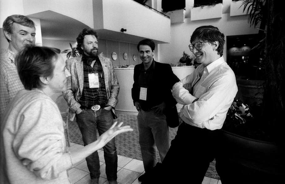 Esther Dyson (left fore), from EDventure Holdings, speaks with Bill Gates (right), from Microsoft, as John Perry Barlow (center, with beard), from Electronic Frontier Foundation/Berkman Center for Internet and Society, and David Readerman (second right), from Shearson Leahman Hutton/Forward Management, along with another, unidentified man, listen during the annual PC Forum, Tucson, Arizona, 1991. Photo: Ann Yow-Dyson/Getty Images, Getty / Photo by Ann Yow-Dyson, all rights reserved