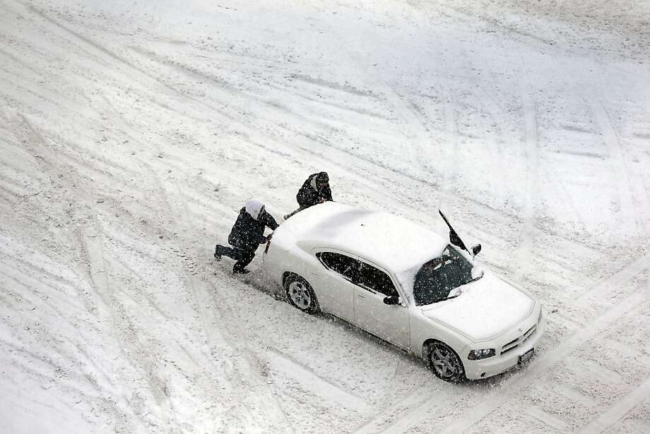 Men help push a car down a slow-covered street in St. Louis., which was hit with a treacherous mixture of snow, sleet and freezing amid warnings from eastern Colorado through Illinois. Photo: Jeff Roberson, Associated Press