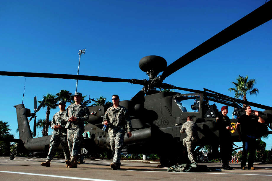 U.S. Army Air Calvary servicemen walk away from an AH-64 Apache helicopter after it landed in the parking lot at the Kemah Boardwalk last November in preparation for the Salute to Military Service weekend. The helo is similar to the one that will be used in today's Army training exercise in Texas City and La Marque. Photo: Johnny Hanson/Houston Chronicle / ONLINE_YES