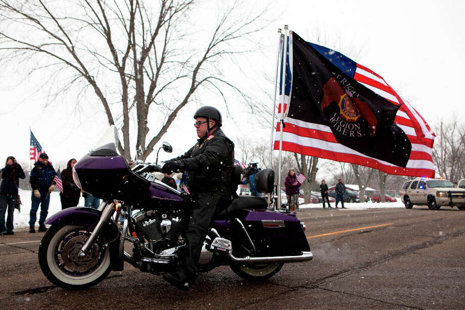 A member of the American Legion Riders rides in the funeral procession for U.S. Army Staff Sgt. Mark Schoonhoven outside St. Margaret's Catholic Church in Otsego, Mich., Thursday, Feb. 7, 2013. Schoonhoven, part of a unit out of Fort Carson, Colo. was wounded Dec. 15 when insurgents attacked his unit with an improvised explosive device in Kabul. He died Jan. 20 at Brooke Army Medical Center at Fort Sam Houston, Texas. (AP Photo/Kalamazoo Gazette, James Buck) Photo: James Buck, Associated Press / Kalamazoo Gazette