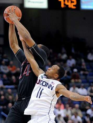 Connecticut's Ryan Boatright, right, reaches for a loose ball with Cincinnati's Kelvin Gaines during the first half of an NCAA college basketball game in Hartford, Conn., Thursday, Feb. 21, 2013. (AP Photo/Fred Beckham)