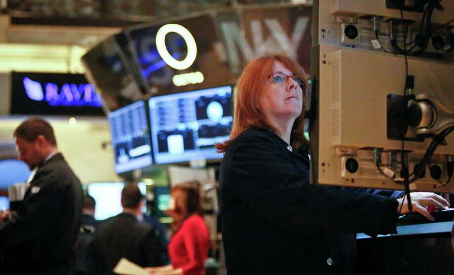 FILE - In this Feb. 20, 2013, file photo, Maureen Smaldone, a trader for Brendan E. Cryan and Company, monitors trading activity from her workstation at the New York Stock Exchange. U.S. stocks are continuing a two-day slide on weak economic data on Thursday, Feb. 21, 2013, and concern that the Federal Reserve may cut back its bond-buying program. (AP Photo/Bebeto Matthews) Photo: Bebeto Matthews