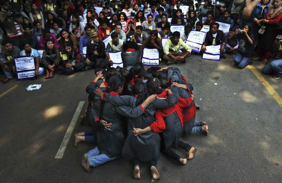 Volunteers huddle during a protest against a new sexual violence law as legislators convene nearby in New Delhi. Activists say the law is inadequate. Photo: Altaf Qadri / Associated Press