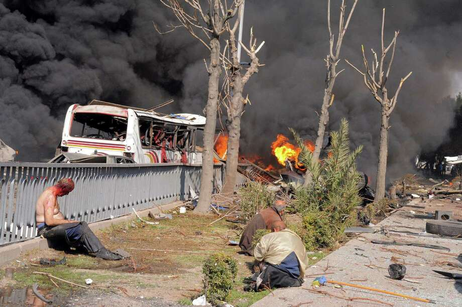 Injured Syrians sit among smoke and flames rising from cars after a huge explosion shook central Damascus, near the headquarters of the ruling party and the Russian Embassy. Photo: SANA / Associated Press