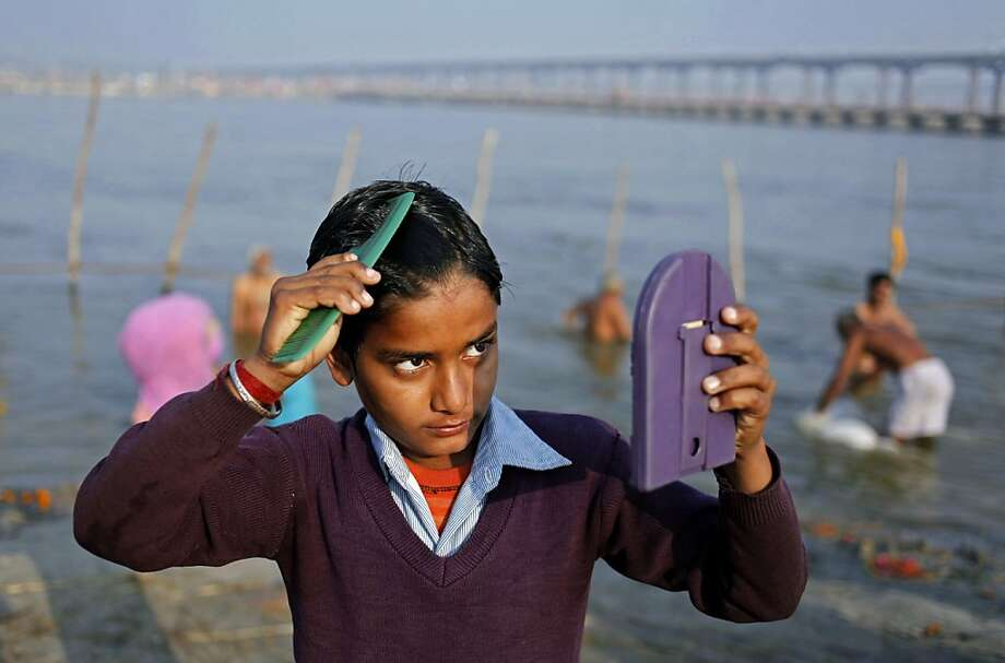 Corporeal grooming after spiritual cleansing:A young Hindu devotee combs his hair after a holy dip at the Sangam, the confluence of the Ganges, Yamuna and mythical Saraswati rivers in Allahabad, India. Photo: Rajesh Kumar Singh, Associated Press