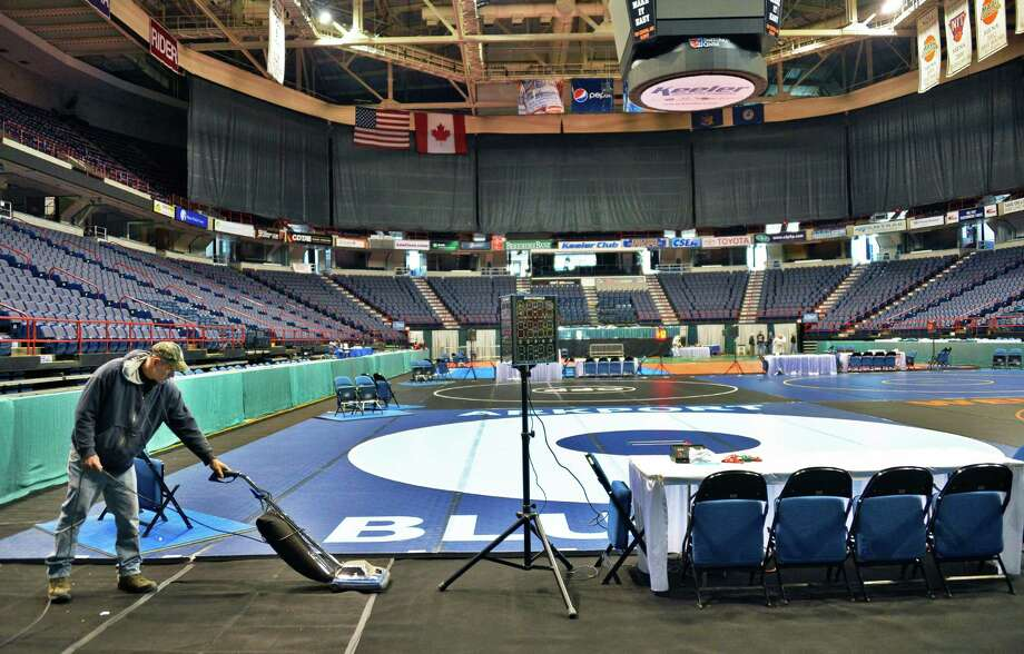 Times Union Center employee Norman Prescott vacuums during set up for this weekend's State wrestling tournament in Albany Thursday Feb. 21, 2013.  (John Carl D'Annibale / Times Union) Photo: John Carl D'Annibale / 00021269A