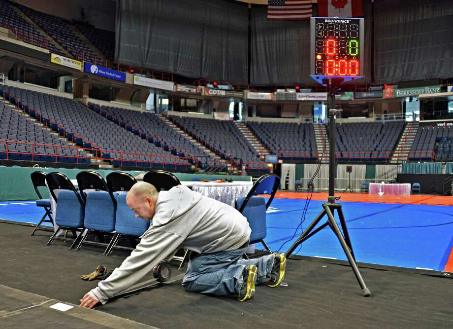 Times Union Center electrician Bob Murdick sets up an officials station for this weekend's State wrestling tournament in Albany Thursday Feb. 21, 2013.  (John Carl D'Annibale / Times Union) Photo: John Carl D'Annibale / 00021269A