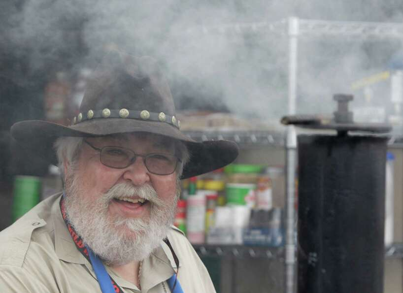 Max Zanger of Houston is surrounded by smoke as he mans the bar-b-que for the Texas Cowtown Cookers