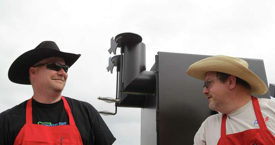 Buns-N-Roses team bar-b-que team members Freddy Jebousek, left, and Joe Conaway both of Magnolia man the pits Thursday, Feb. 21, 2013, in Houston.  The World's Championship Bar-B-Que contest kicks-off the Houston Livestock Show and Rodeo at Reliant Park. Photo: Melissa Phillip, Houston Chronicle / © 2013  Houston Chronicle
