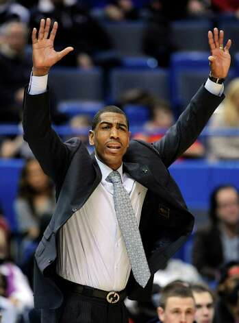 Connecticut coach Kevin Ollie signals to his team during the first half of an NCAA college basketball game against Cincinnati in Hartford, Conn., Thursday, Feb. 21, 2013. (AP Photo/Fred Beckham) Photo: Fred Beckham, Associated Press / FR153656 AP