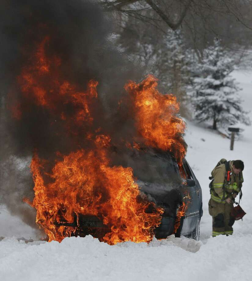 A Lawrence, Kan., firefighter prepares to extinguish a car, which caught on fire trying to make it up a snow-covered hill on Lawrence Avenue and became engulfed in flames. Photo: Orlin Wagner / Associated Press