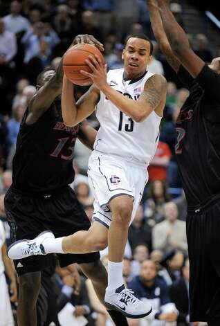 Connecticut's Shabazz Napier drives past Cincinnati's Titus Rubles, right, and Cheikh Mbodj late in the second half of an NCAA college basketball game in Hartford, Conn., Thursday, Feb. 21, 2013. Napier scored a game-high 27 points in his team's 73-66 overtime victory. (AP Photo/Fred Beckham) Photo: Fred Beckham, Associated Press / FR153656 AP