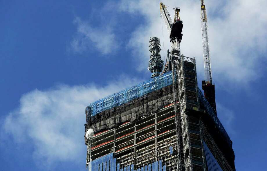 A crane on the top of One World Trade Center works next to a spire, Thursday, Feb. 21, 2013 in New York. The spire will bring the skyscraper to a height of 1776 feet (541 meters). (AP Photo/Mark Lennihan) Photo: Mark Lennihan