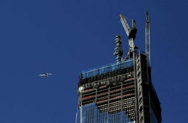 A jet plane flies above One World Trade Center, Thursday, Feb. 21, 2013 in New York. A crane works next to the rising spire that will bring the skyscraper to a height of 1776 feet (541 meters). (AP Photo/Mark Lennihan) Photo: Mark Lennihan