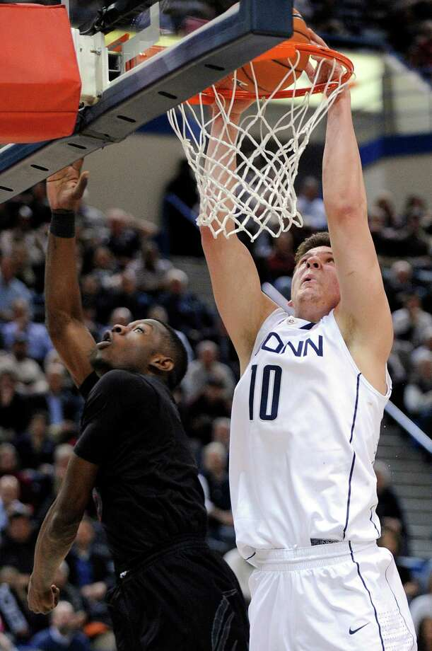 Connecticut's Tyler Olander, right, scores over Cincinnati's Justin Jackson during the second half of Connecticut's 73-66 overtime victory in an NCAA college basketball game in Hartford, Conn., Thursday, Feb. 21, 2013. (AP Photo/Fred Beckham) Photo: Fred Beckham, Associated Press / FR153656 AP